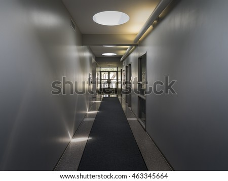 Point of view looking down empty offices hallway toward glass doors. / Hallway with Direct and Indirect Light #463345664