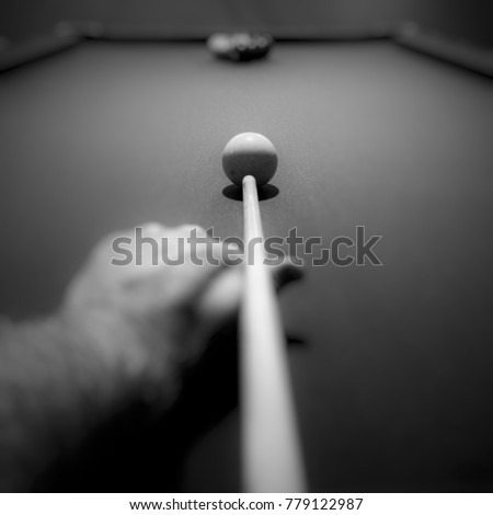 Point of view looking down pool stick aimed at cue ball. Focus is at end of stick and cue ball. Keep your eye on the ball. Focus on what matters. #779122987