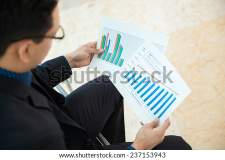 Point of view of a businessman looking at a couple of charts and reviewing performance