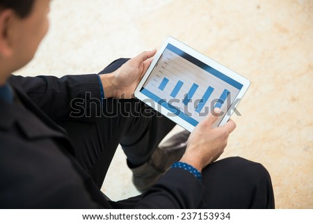 Point of view of a businessman using a tablet computer to analyze some performance charts
