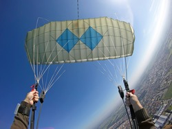 Point of view of skydiver piloting his parachute. Fish eye lens used. Sunshine right image .