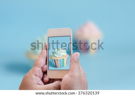 Point of view of woman taking a photo of her cupcake with her smartphone. Picture of food on screen.