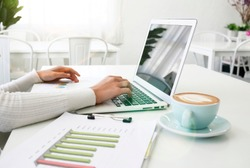 Point of view of young entrepeneur holding paperwork with colorful graphics. White desk with computer.