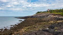 Point Prim Lighthouse as seen from the rocky beach below during low tide. Located near Digby, Nova Scotia.