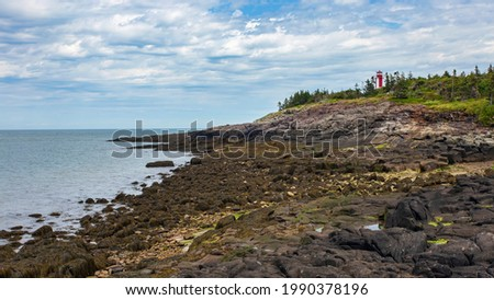 Point Prim Lighthouse as seen from the rocky beach below during low tide. Located near Digby, Nova Scotia. Stock foto ©