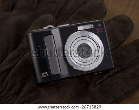 Point & Shoot Digital Camera placed on leather gloves