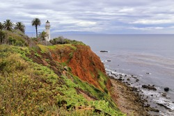 Point Vicente Lighthouse stands atop a bluff under cloudy skies on Southern California's coastline.