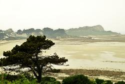 Pointe de Primel, Primel-Trégastel, Finistère, France. Atlantic Ocean. overcast Landscape at the coast at Pointe de Primel in Finistere Brittany France. Interplay Of High And Low Tide (Ebb And Flow)