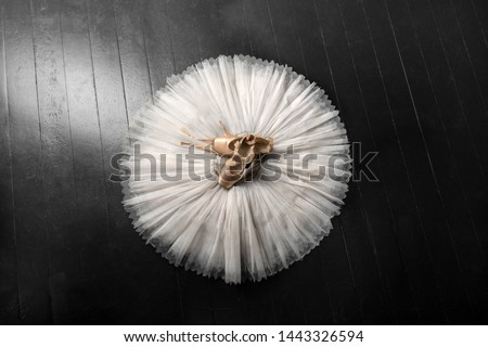 Pointe shoes. Peach shoes, ballet shoes with ribbons on a white tutu in a dance studio. Advertising ballet school. Professional ballerina outfit. Foto stock ©