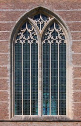 Pointed ogive arch with gothic window at the brick facade of Brouwershaven city church in the Netherlands