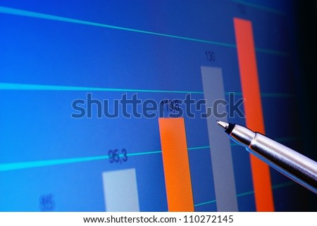 Pointing at financial analysis graph on computer monitor with pen