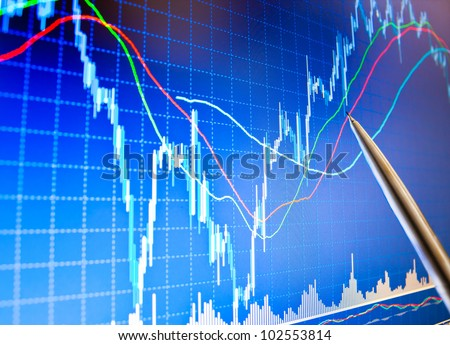 Pointing at financial graph on a computer monitor screen with pen - stock photo