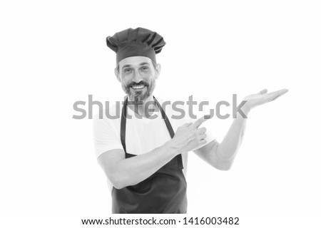 Pointing at something. Senior cook with beard and moustache wearing bib apron. Bearded mature man in chef hat and apron. Mature chief cook in red cooking apron. Presenting product, copy space. #1416003482