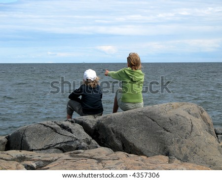 Pointing girl and sitting boy by the ocean