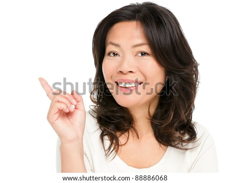 Pointing showing Asian woman. Middle aged Chinese Asian woman pointing and showing smiling happy. Female model in her early 50s isolated on white background.
