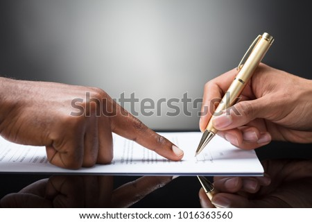 Pointing The Finger In Front Of A Person Signing With Golden Pen On The Document