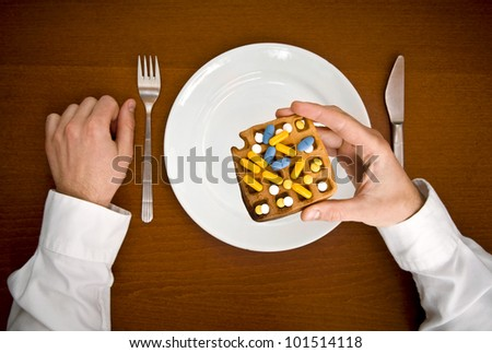 Poisons for eating. Human hand hold waffle with pills from top view.