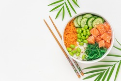 Poké bowl with fresh salmon, rice, chukka salad, edamame beans, carrots and cucumber. Bowl of healthy food on white background
