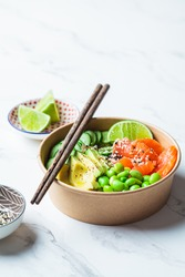 Poke bowl with rice, salmon, edamame beans, cucumber and avocado in a reusable cardboard bowl. Hawaiian food. Zero Waste concept.
