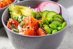 Poke bowl with salmon, rice, avocado, edamame beans, cucumber and radish in a gray bowl. Hawaiian ahi poke bowl, gray background.