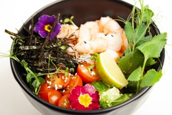 Poke salad with shrimp in a bowl. Ingredients Shrimp, blanched spinach, cherry tomatoes, rice, cucumber, soy-ginger sauce, Spicy sauce, nori, sesame, lime, cilantro. Asian seafood salad concept.
