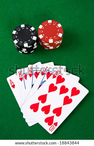 Poker arrangement with poker chips on green poker table.
