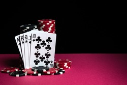 Poker cards with a royal flush combination. Close-up of playing cards and chips in casino. Free advertising space