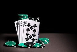 Poker cards with a royal flush combination. Closeup of playing cards and chips in poker club. Dark background with advertising space