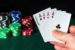 Poker cards with five of a kind highest combination in the game. Close-up of a gambler hand is holding playing cards in poker club. Chips on the green table