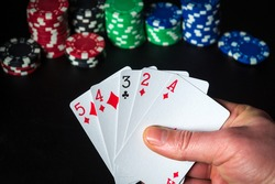 Poker cards with high card combination. Close up of a gambler hand is holding playing cards in casino