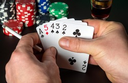 Poker cards with high card combination. Close up of a gambler hands is holding playing cards in poker club