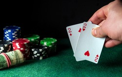 Poker cards with one pair combination in the game. Close-up of a gambler hand is holding playing cards in poker club. Chips on the green table