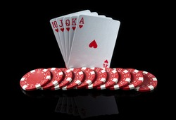 Poker cards with royal flush combination. Close-up of playing cards and chips in poker club. Free advertising space