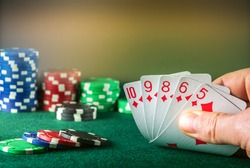 Poker cards with straight flush combination. Close up of gambler hand takes playing cards in poker club