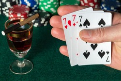 Poker cards with three of a kind or set  combination. Close up of a gambler hand is holding playing cards in poker club