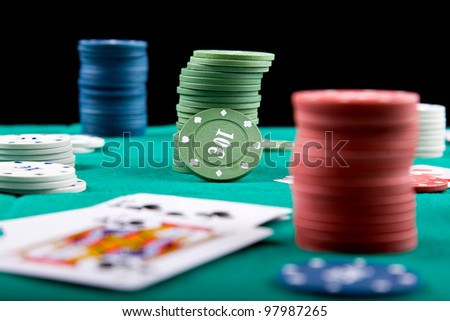 Poker chips and cards on a green felt