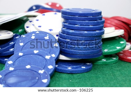 Poker chips and cards on a green felt top table.