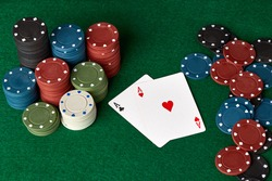 Poker chips and cards on a green poker canvas. Gambling, poker, casino concept. Black background. Close-up.