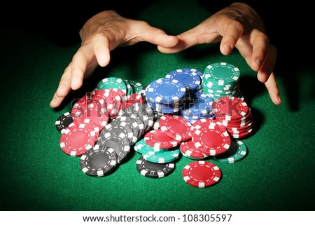 Poker chips and hands above it on green table