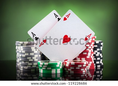Poker chips and playing cards on green background