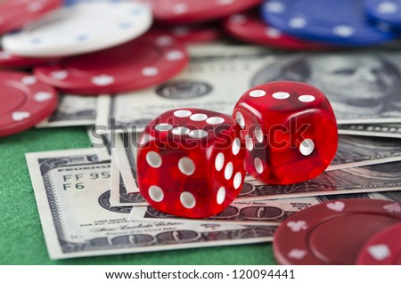 Poker chips, money and dice on green background
