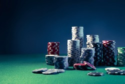 Poker Chips on a gaming table with dramatic lighting