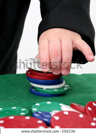 Poker chips on a green felt top table being stacked by a child\'s hand.