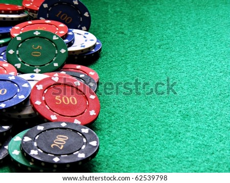 Poker chips on green felt table with copy space