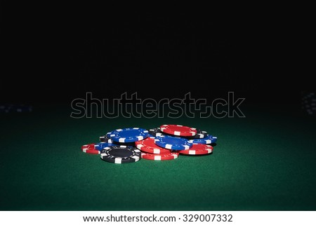 Poker chips on table in casino with black background