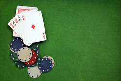 Poker cloth, a deck of cards, poker hand and chips. Background.