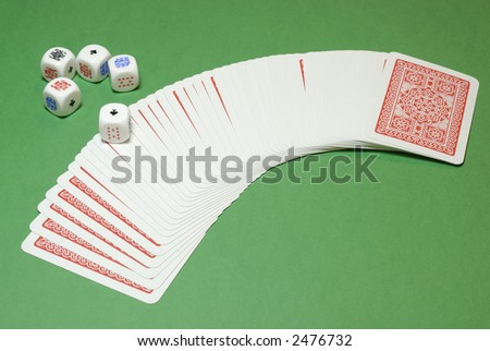 Poker dices and a cards deck on a casino table background