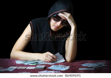 Poker face. Person in sun glasses and hood playing poker at the table with cards and money