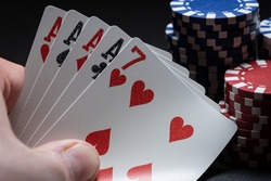 Poker game showing a hand holding a poker of 4 aces and a 7 of red hearts. Poker chips of different colors in the background.