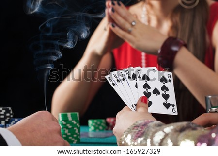 Poker game with drinks and cigarettes in casino